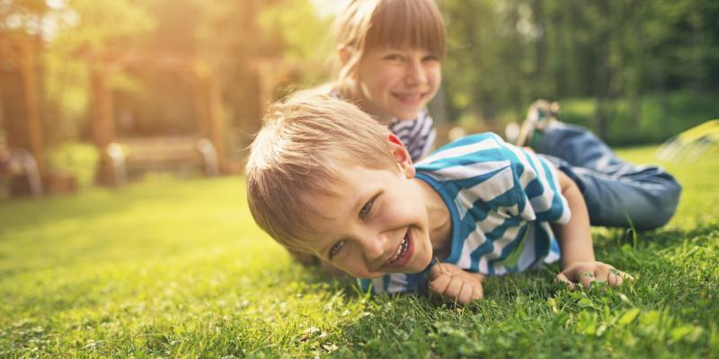 a young boy and a young girl siblings playing in the grass and smiling